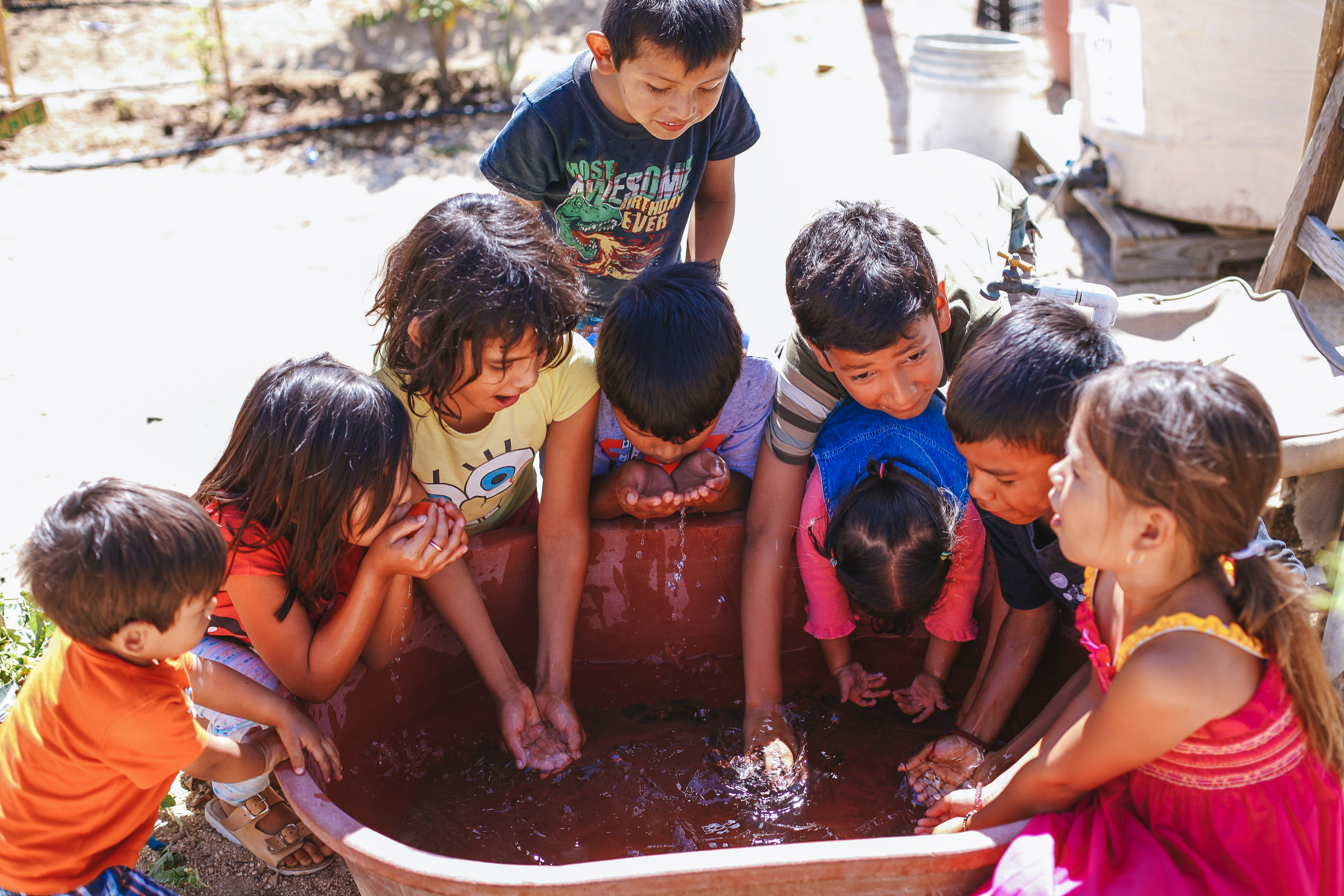 Children wash their hands in a tub full of water